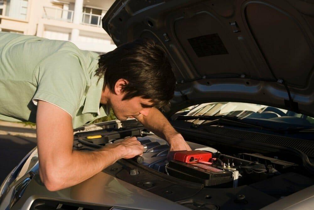 man checking car under the hood